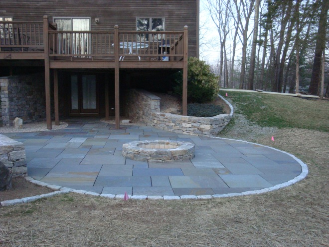 The circular shape centers on the firepit. The curved edges lead also the eyes into the house entrance